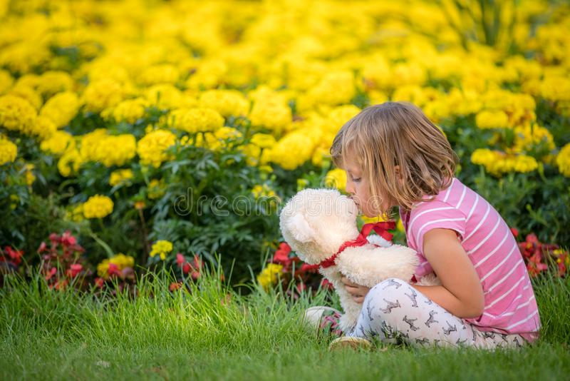 亲吻她喜爱的玩具熊的可爱的小孩女孩 免版税图库摄影