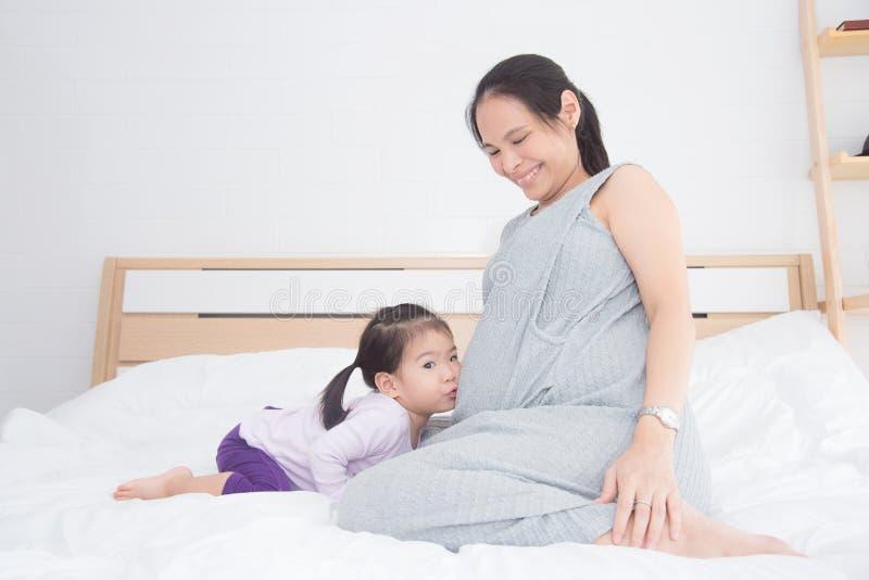 亲吻她在床上的小女孩怀孕的母亲腹部 免版税库存照片