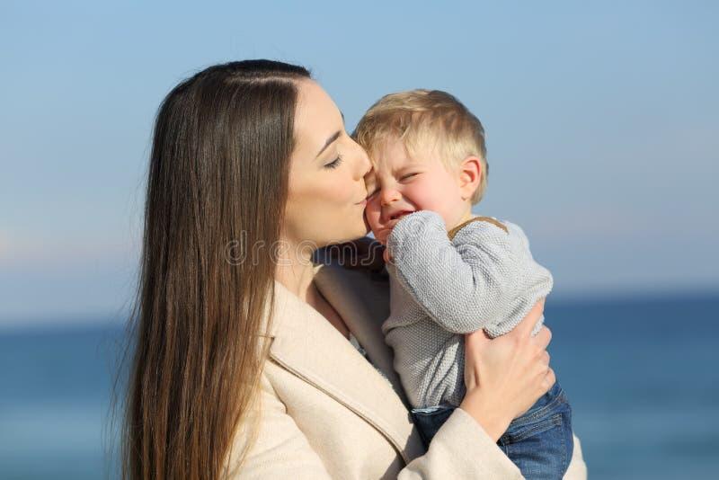 亲吻她恼怒的儿子的母亲 库存照片