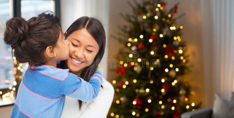 亲吻她的圣诞节的愉快的女儿母亲 免版税库存照片