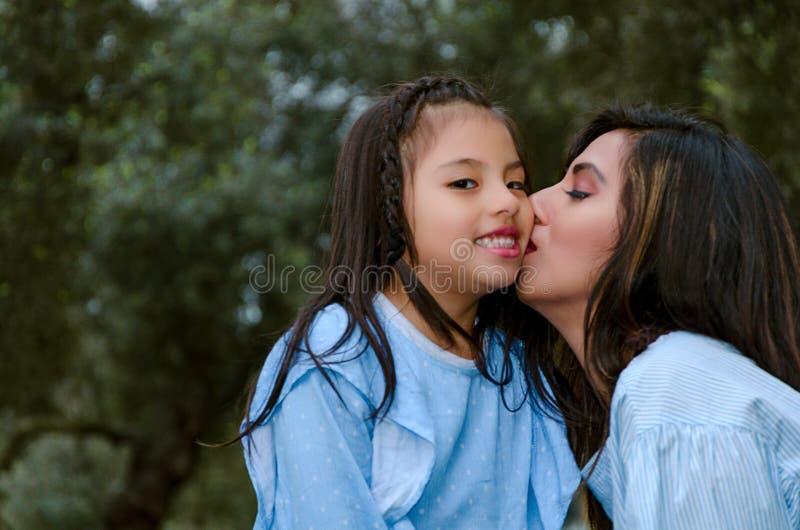 亲吻她的女儿的愉快的母亲享受冬天下午 免版税图库摄影