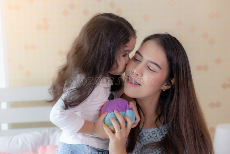 亲吻她的妈妈的可爱的女孩在给的爱面颊她美丽的母亲 亚裔母亲得到幸福,当她逗人喜爱 库存照片