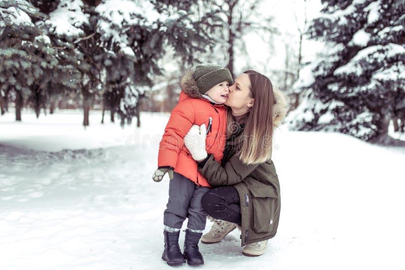 亲吻她的孩子,3-5岁的男孩的一个年轻母亲,在冬天在森林,反对背景雪漂移积雪 免版税库存图片