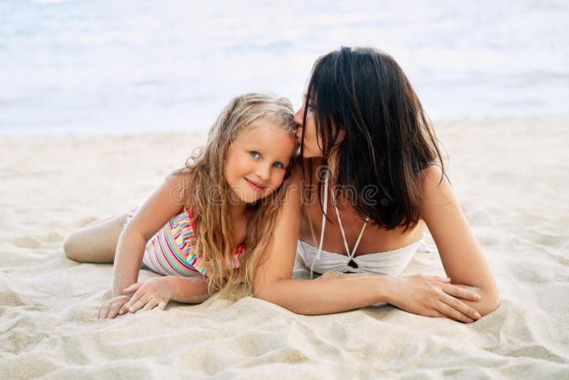 亲吻她的小女儿的年轻美女放松在热带海滩在暑假 图库摄影