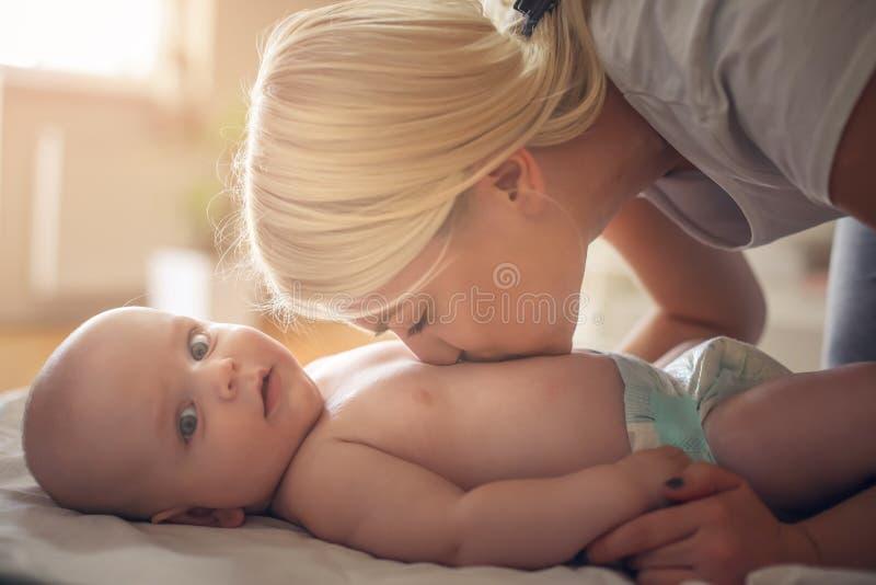 亲吻她的尿布的年轻母亲小婴孩 关闭 免版税库存照片