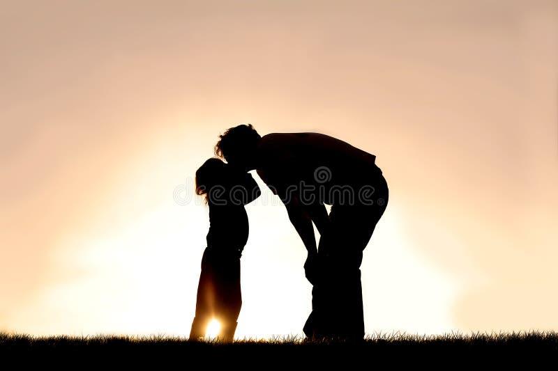 亲吻她的父亲的小孩剪影在日落在一个夏日 免版税库存照片