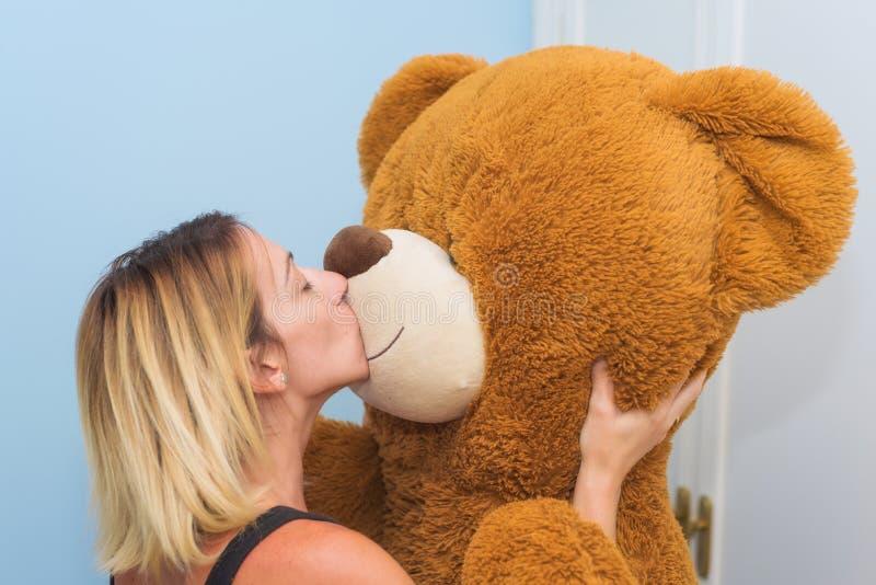 亲吻她的玩具熊的一名美丽的妇女的画象 库存照片