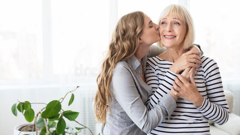 亲吻她的面颊的女儿成熟母亲 库存图片
