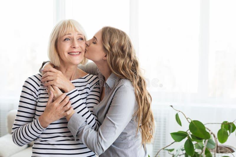 亲吻她的面颊的年轻女人母亲 免版税库存图片