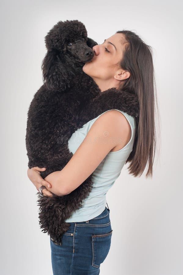 亲吻她美丽的狗的一个美丽的少妇的画象 免版税库存图片