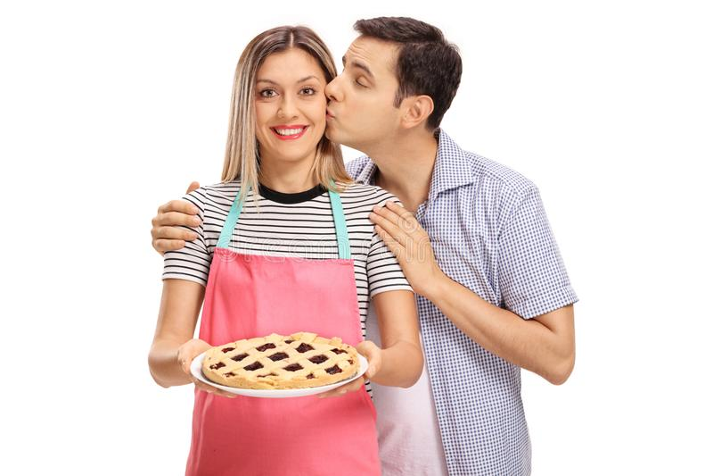亲吻妇女的年轻人拿着一个新近地被烘烤的饼 库存照片