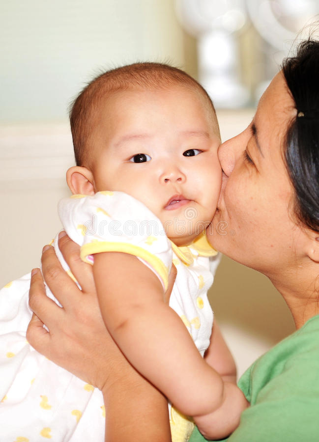 亲吻妈妈的婴孩 免版税图库摄影