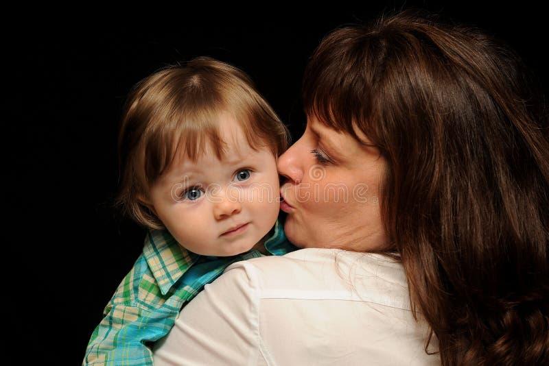 亲吻妈妈的婴孩 免版税库存图片