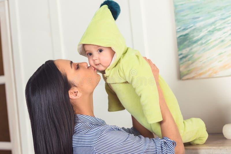 亲吻婴儿婴孩的母亲侧视图 免版税库存照片