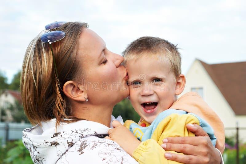 亲吻婴孩的愉快的母亲 免版税库存图片