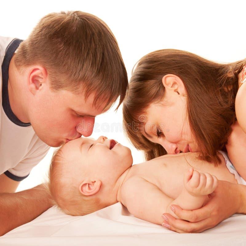 亲吻婴孩的父项。 免版税库存照片