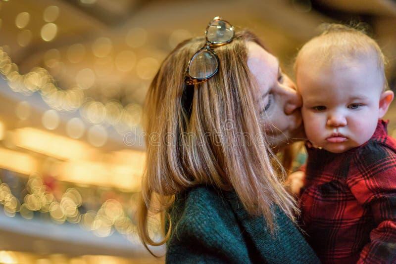 亲吻孩子的妇女在的圣诞前夕教会里 库存图片