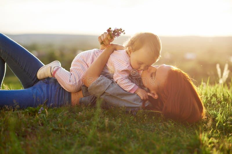 亲吻小女儿的年轻母亲说谎在草 库存图片