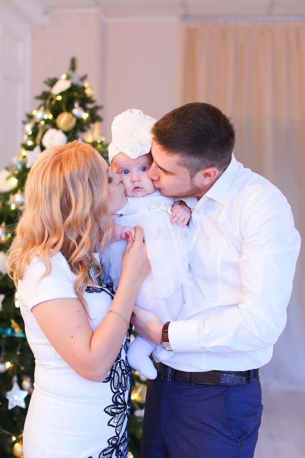 亲吻小女儿的年轻父母在圣诞树附近 库存照片