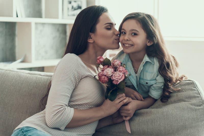 亲吻小女孩的少妇拿着花 库存图片