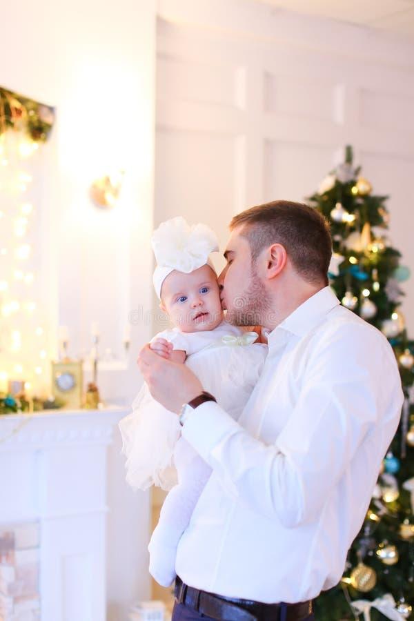 亲吻小女性婴孩的年轻父亲在圣诞树附近 免版税图库摄影