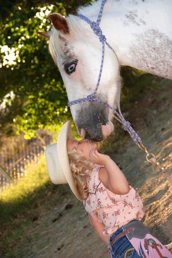 亲吻小的小马的女孩 免版税库存照片