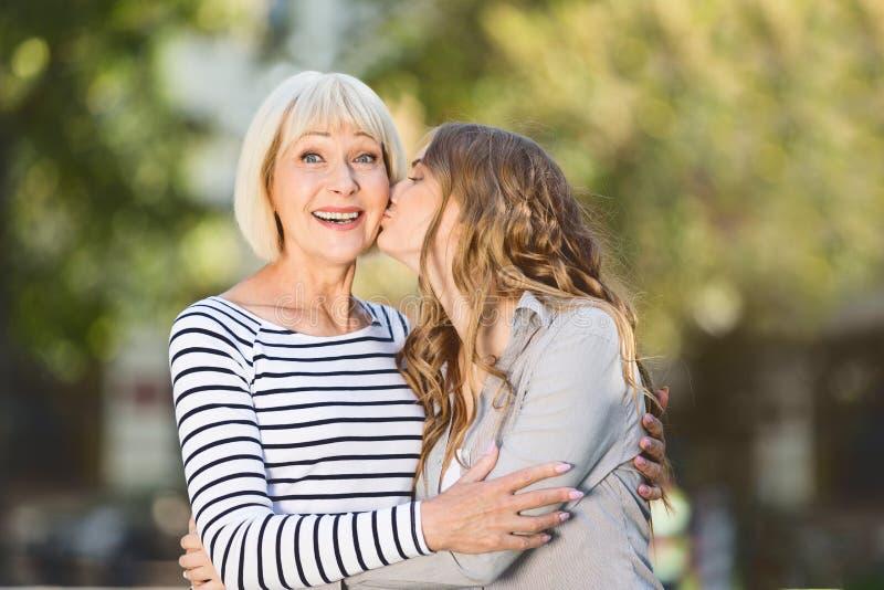 亲吻年长母亲的妇女户外在好日子 库存照片