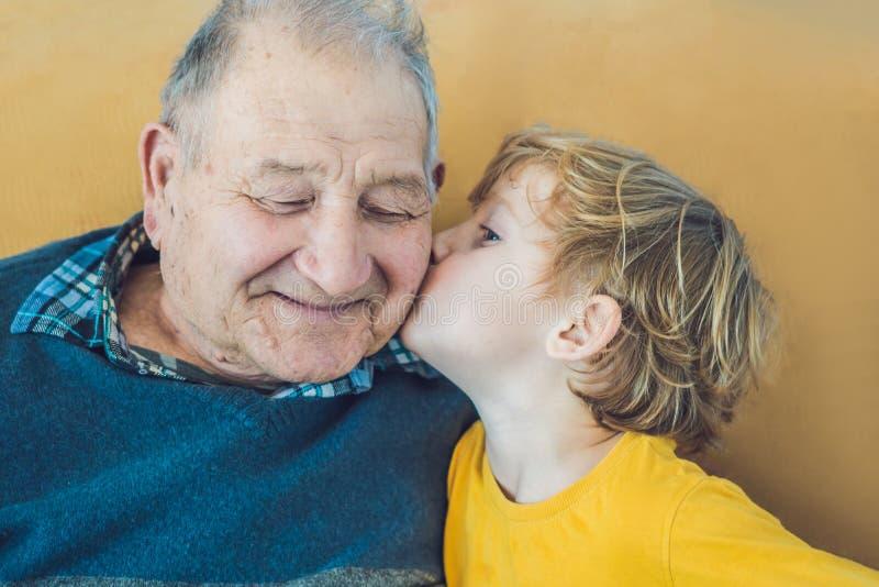 亲吻愉快的爷爷的一个愉快的男孩的画象 免版税库存照片
