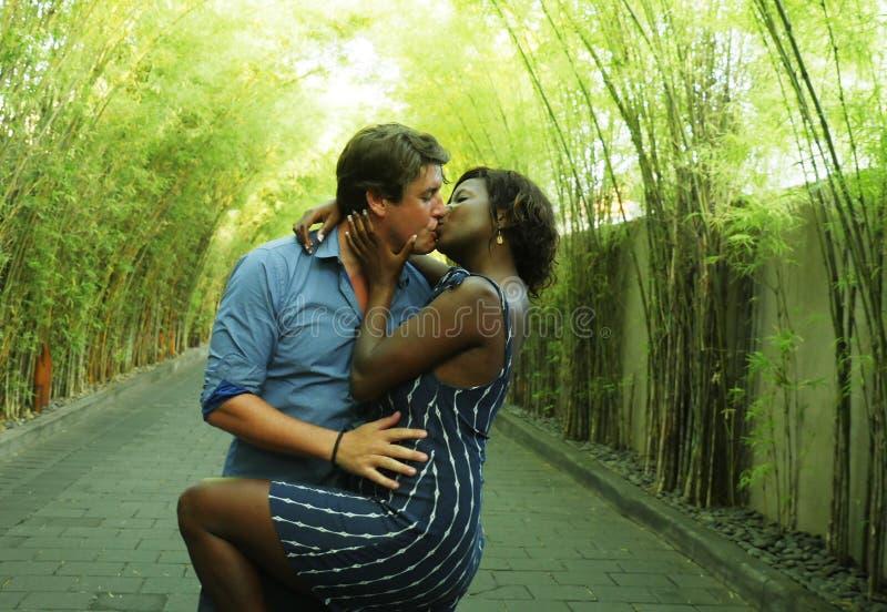 亲吻户外与可爱的黑人非裔美国人的女朋友的愉快的混杂的种族夫妇或妻子和英俊的白种人人 免版税库存照片
