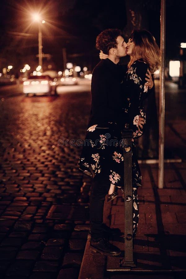 亲吻户外在街道,在n的两个恋人亲吻的性感的夫妇 免版税图库摄影