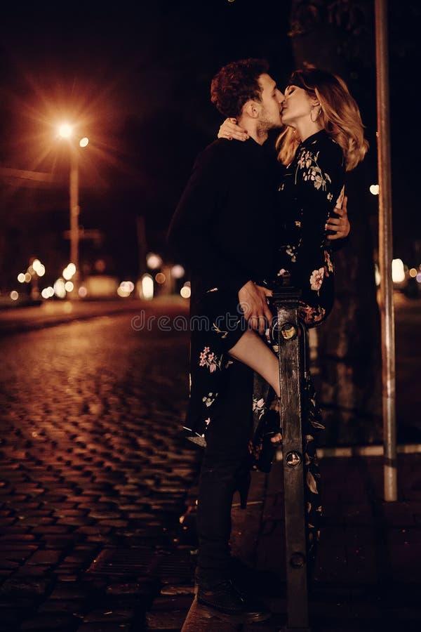 亲吻户外在街道,在n的两个恋人亲吻的性感的夫妇 图库摄影