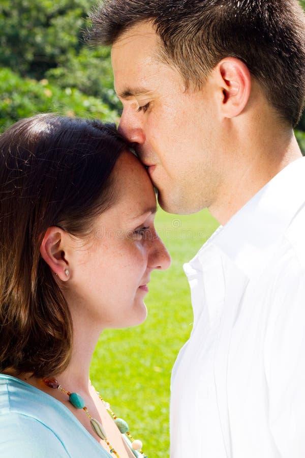 亲吻户外年轻人的夫妇 库存图片