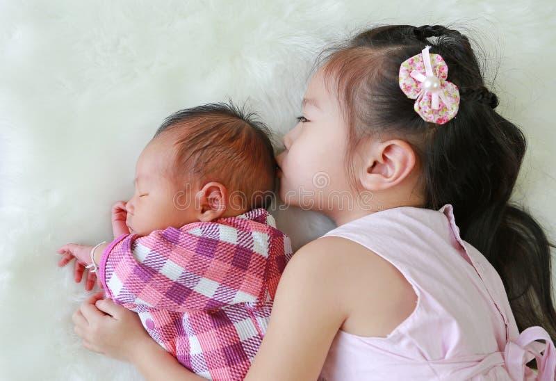 亲吻新生儿的可爱的亚裔姐妹说谎在白色毛皮背景 库存图片
