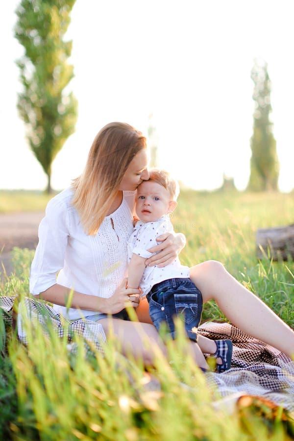 亲吻格子花呢披肩的,在背景的草的年轻白肤金发的母亲小孩 免版税库存图片