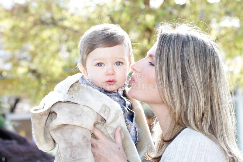 亲吻母亲儿子的婴孩 免版税库存照片