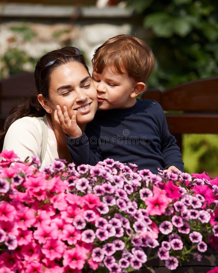 亲吻母亲的孩子室外 库存照片