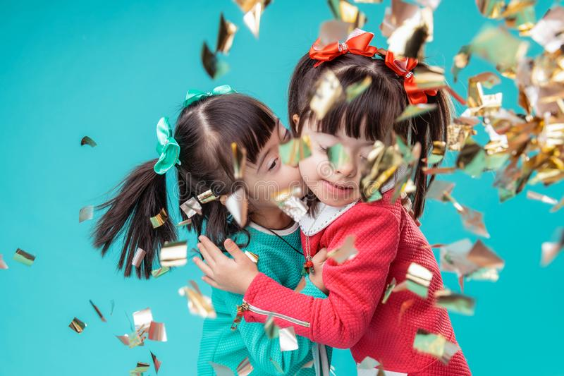 亲吻的深色头发的正面姐妹,当站立时 免版税库存照片