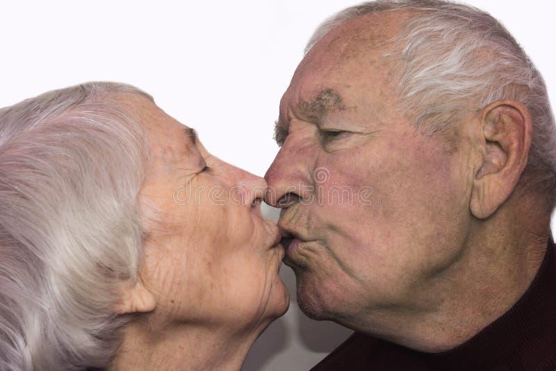 亲吻老人的资深妇女 免版税库存图片