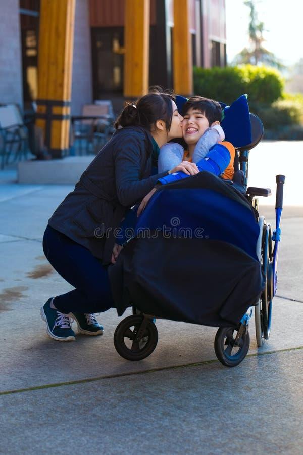 亲吻轮椅的更老的姐妹小残疾兄弟胜过 免版税图库摄影