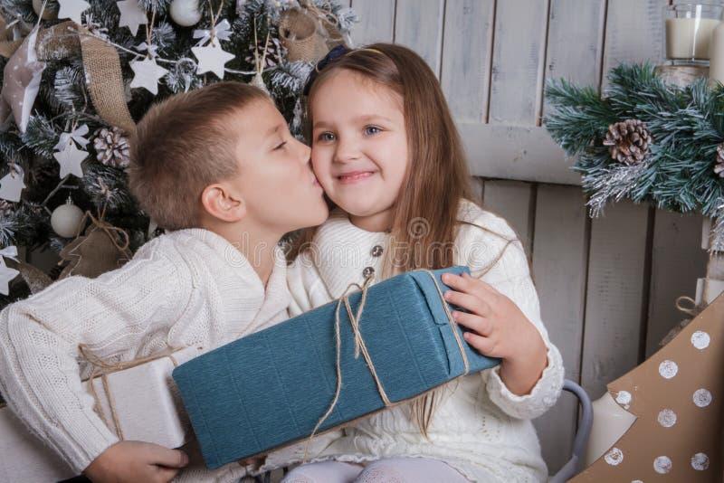 亲吻面颊的男孩女孩与圣诞节礼物 库存照片