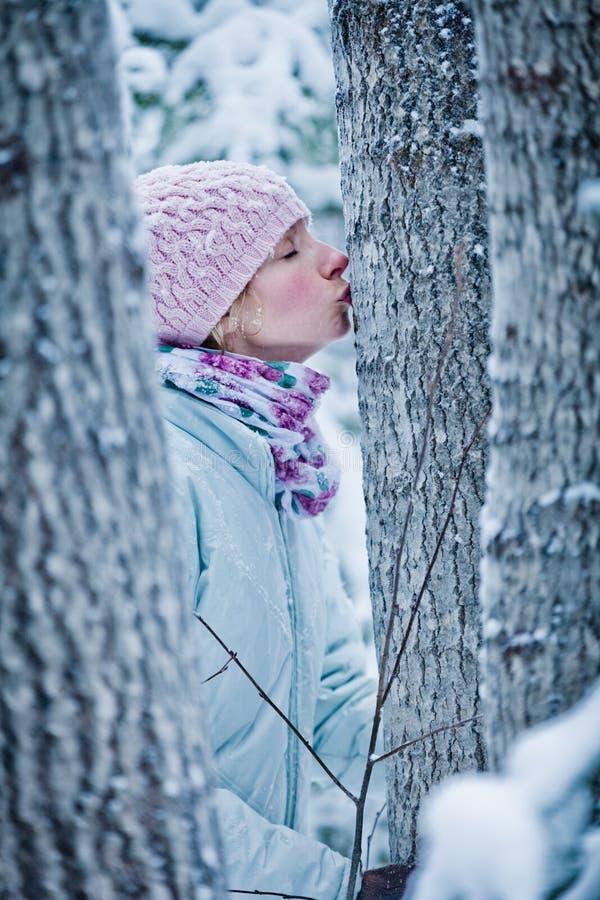 亲吻一棵树的可爱的女孩在森林里 免版税图库摄影