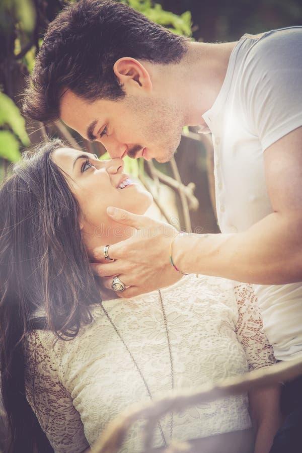 亲吻 年轻人和年轻微笑的妇女夫妇 免版税库存照片