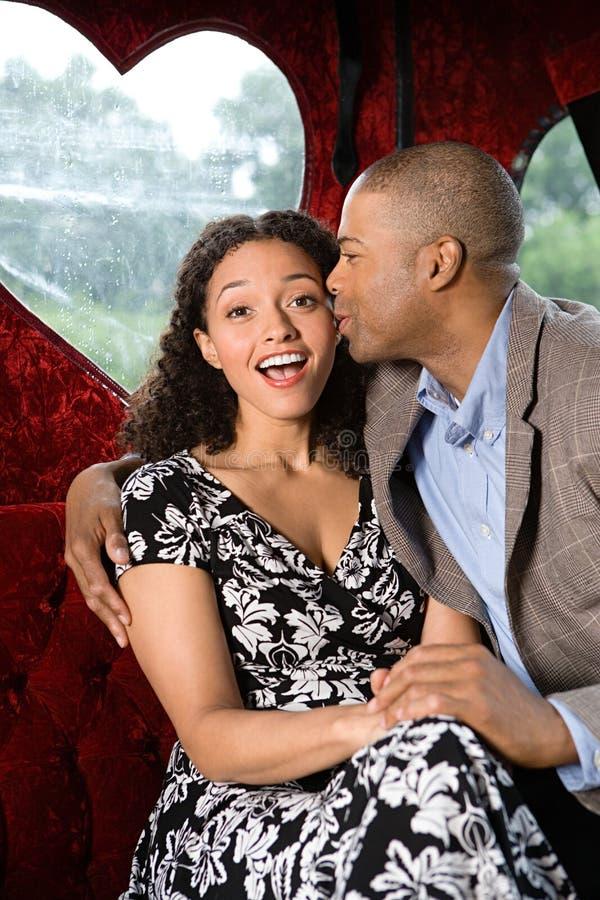 亲吻人妇女的面颊 免版税库存照片