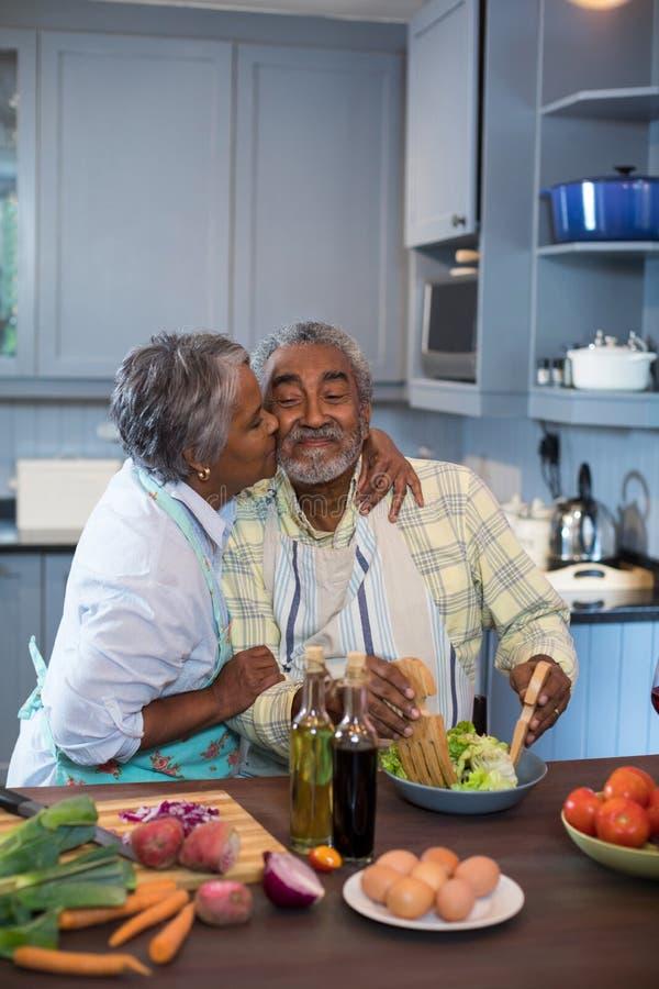 亲吻人的妇女侧视图,当准备食物时 图库摄影