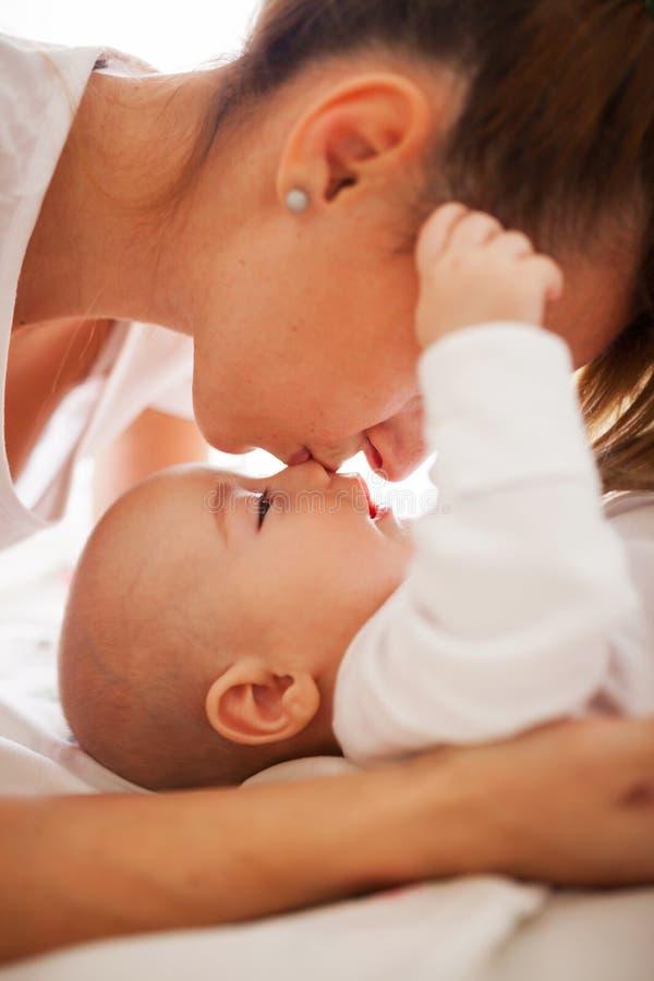 亲吻儿子的鼻子的母亲 免版税库存图片