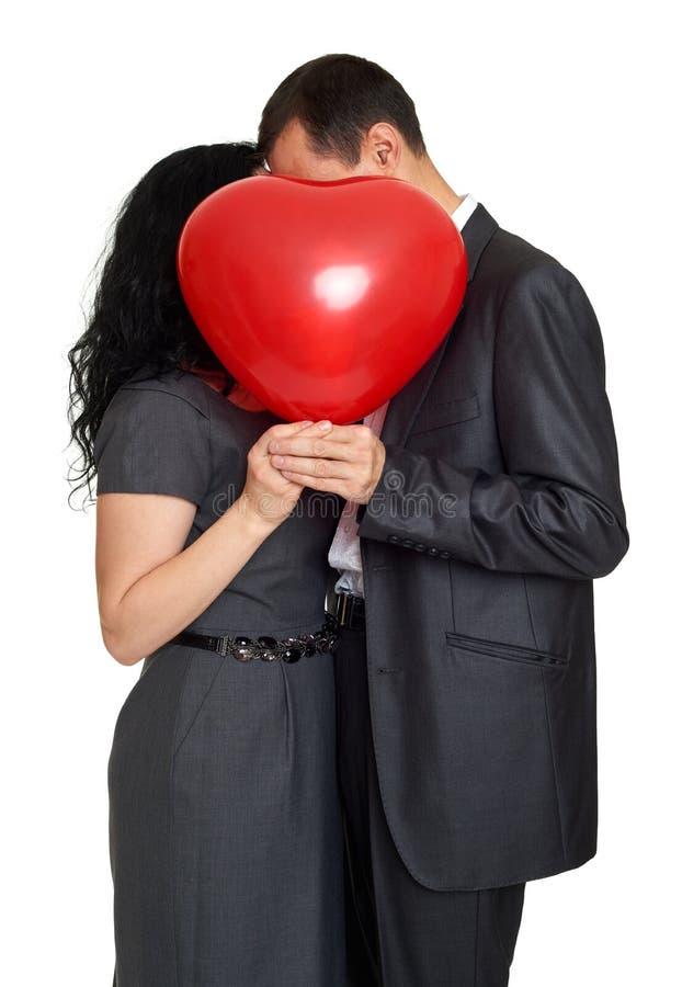 亲吻和掩藏在红色心形的气球后的愉快的夫妇 华伦泰假日概念 查出的工作室 免版税库存图片