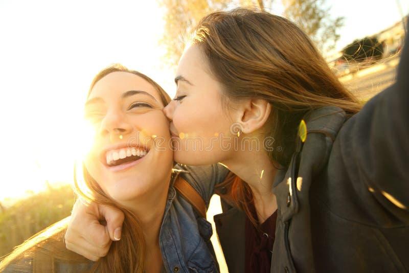 亲吻和采取selfie的富感情的朋友 免版税库存图片
