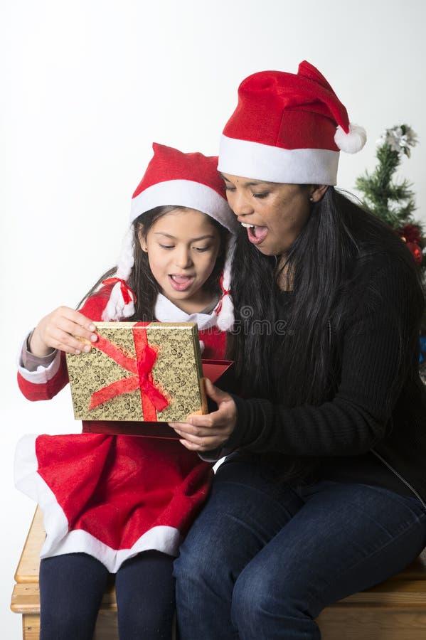亲吻和给Xmas的小女孩和母亲当前 免版税库存图片