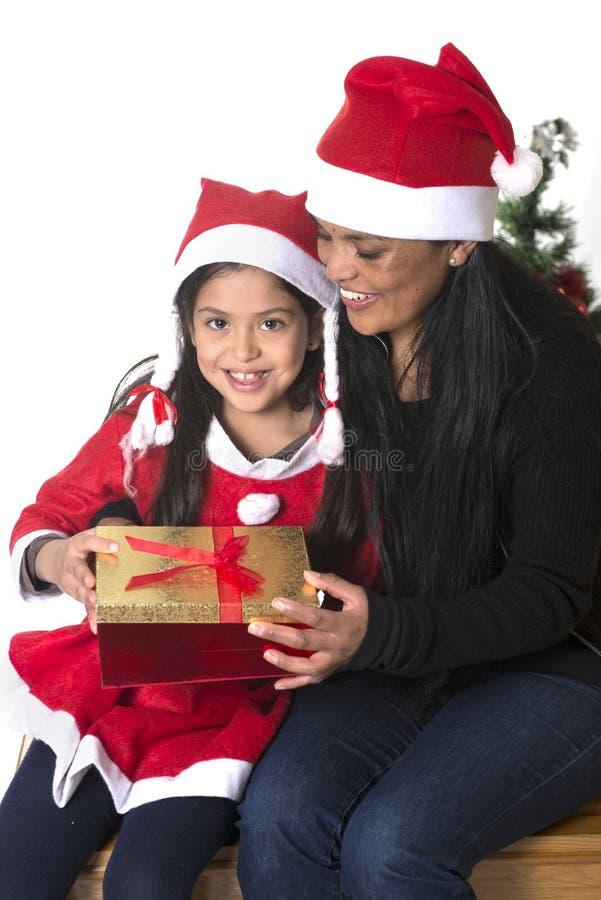 亲吻和给Xmas的小女孩和母亲当前 图库摄影