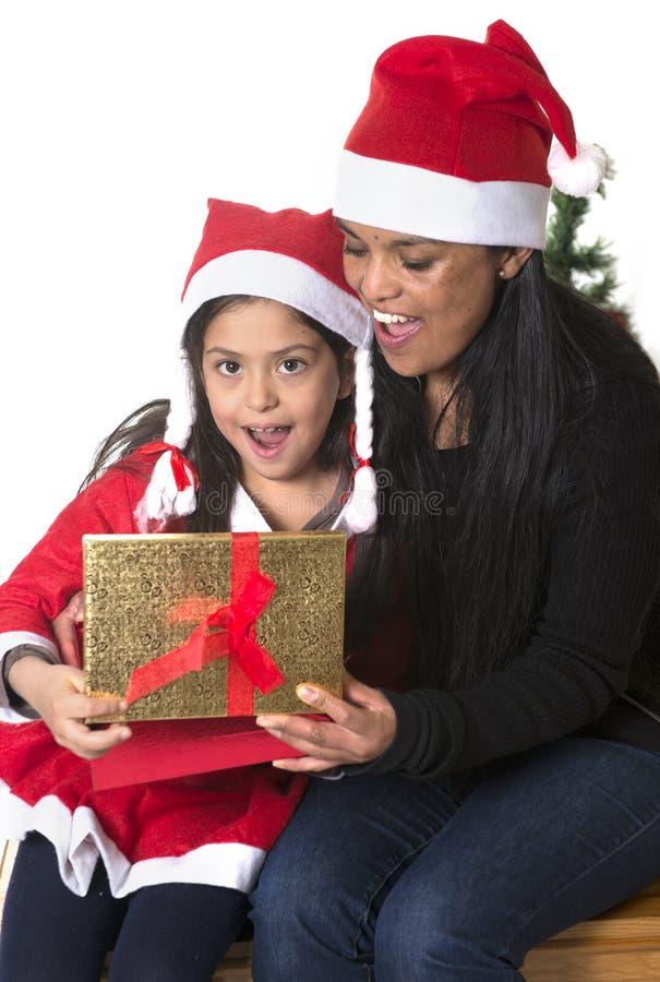 亲吻和给Xmas的小女孩和母亲当前 免版税库存照片
